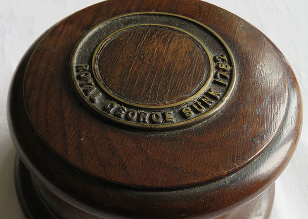 Cylindrical wooden lidded box with the words 'Royal George sunk 1782' carved on the lid